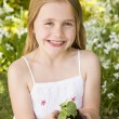 Stock Photo: Young girl outdoors holding plant smiling
