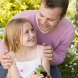 Father and daughter outdoors holding plant smiling - Stock Photo