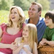 Family sitting outdoors with picnic basket smiling — Stock Photo #4771019