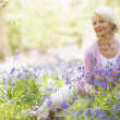 Woman sitting outdoors with flowers smiling - Stock Photo