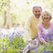 Couple sitting outdoors with flowers smiling — Stock Photo #4771046