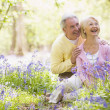 Couple sitting outdoors with flowers smiling — Stock Photo
