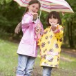 Two sisters outdoors in rain with umbrella smiling — Stock Photo #4771061