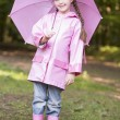 Young girl outdoors with umbrella smiling - Stock Photo
