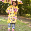 Young girl outdoors in rain with umbrella smiling - Stock Photo