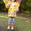 Stock Photo: Young girl outdoors with umbrelljumping and smiling