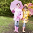 Stock Photo: Two sisters outdoors with umbrellas smiling