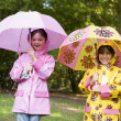 Two sisters outdoors in rain with umbrellas smiling - Stock Photo