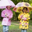 Two sisters outdoors in rain with umbrellas smiling — Stock Photo #4771069