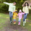 Family outdoors skipping with umbrella smiling - Stock Photo