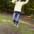 Woman outdoors jumping with umbrella smiling — Stock Photo