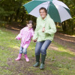 Father and daughter outdoors with umbrella smiling - Stock Photo