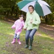 Stock Photo: Father and daughter outdoors with umbrellsmiling