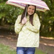 Woman outdoors in rain with umbrella smiling - Stock Photo