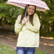 Stock Photo: Womoutdoors in rain with umbrellsmiling