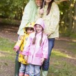 Family outdoors in rain with umbrella smiling - Stock Photo