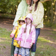 Стоковое фото: Family outdoors in rain with umbrella smiling