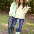 Couple outdoors in rain with umbrella smiling — Stock Photo