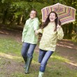 Stock Photo: Couple outdoors running with umbrellsmiling