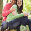 Couple outdoors in woods sitting on log smiling - Lizenzfreies Foto