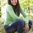 Stock Photo: Womoutdoors in woods sitting on log smiling
