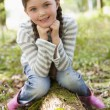 Stock Photo: Young girl outdoors in woods sitting on log smiling