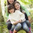 Stock Photo: Mother and daughters outdoors in woods sitting on log smiling