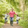 Stock Photo: Father and daughters walking on path holding hands smiling
