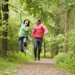 Couple jumping on path holding hands and smiling — Foto Stock