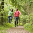 Couple jumping on path holding hands and smiling — Stockfoto