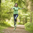 Stock Photo: Womjumping on path smiling