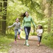 Mother and daughters skipping on path smiling — Stock Photo #4771121