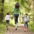Stock Photo: Mother and daughters skipping on path smiling