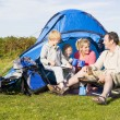 Family camping with tent and cooking - Stock Photo