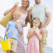 Family standing at beach with ice cream smiling — Stock Photo #4771126