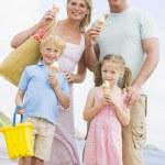 アイスクリームを笑顔でビーチで家族に立って — ストック写真