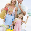 Family standing at beach with ice cream smiling — Stock Photo