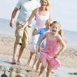 Family running at beach smiling — 图库照片