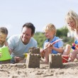 Family on beach making sand castles smiling — Foto Stock
