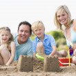 Family on beach making sand castles smiling — Stok fotoğraf
