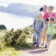 Family walking on cliffside path pointing and smiling - Stockfoto