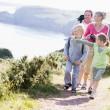 familia caminando por sendero cliffside apuntando y sonriendo — Foto de Stock   #4771149