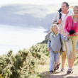 Family walking on cliffside path holding hands and smiling — Stock Photo #4771150