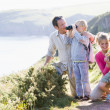 Family on cliffside path using binoculars and smiling — Stock Photo #4771155
