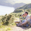 Family on cliffside path using binoculars and smiling — Stock Photo