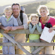 Family on cliffside path leaning on fence and smiling — Stock Photo