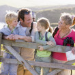 Family on cliffside path leaning on fence and smiling — Stock Photo #4771163