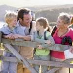フェンスの上に傾いたと笑みを浮かべてクリフサイド パス上の家族 — ストック写真