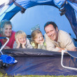 Family camping in tent smiling — Stock Photo