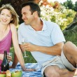 Couple sitting outdoors with picnic smiling — Stock Photo